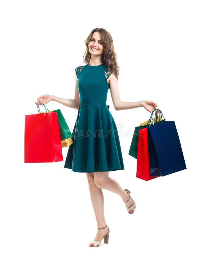 拿着许多五颜六色的购物袋isolat的愉快的美丽的妇女 库存图片