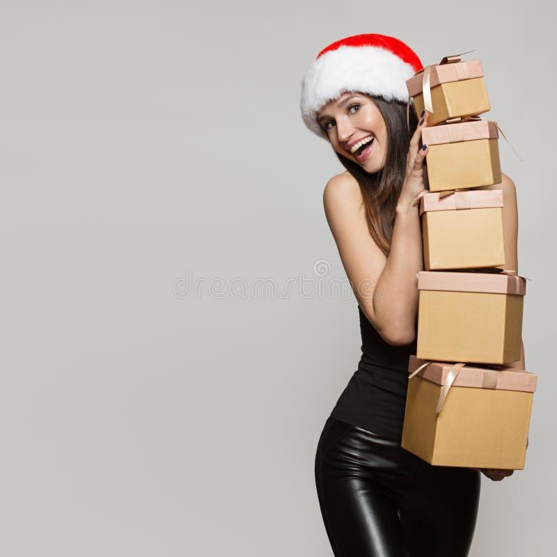 拿着许多礼物盒的圣诞老人帽子的愉快的妇女 免版税库存照片