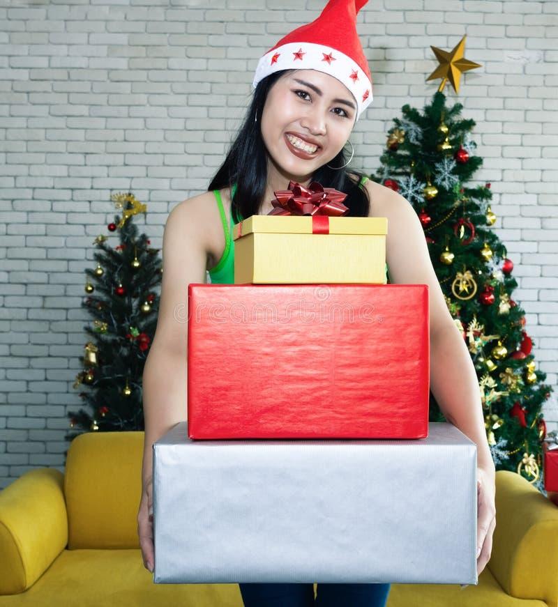 拿着许多礼物盒的微笑的含沙女孩 库存照片