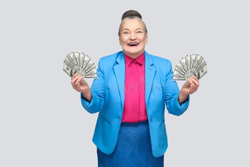 拿着许多美国美元的愉快的年迈的妇女 库存图片