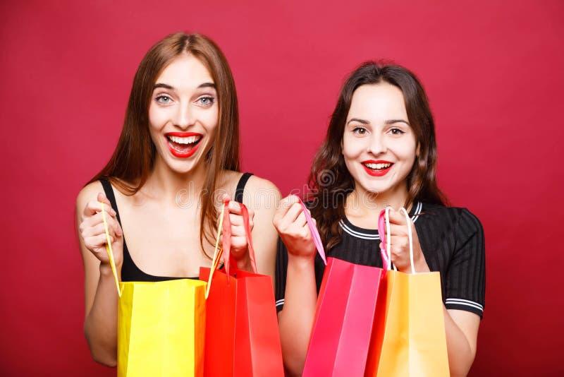拿着许多购物袋的两个逗人喜爱的女朋友 库存图片