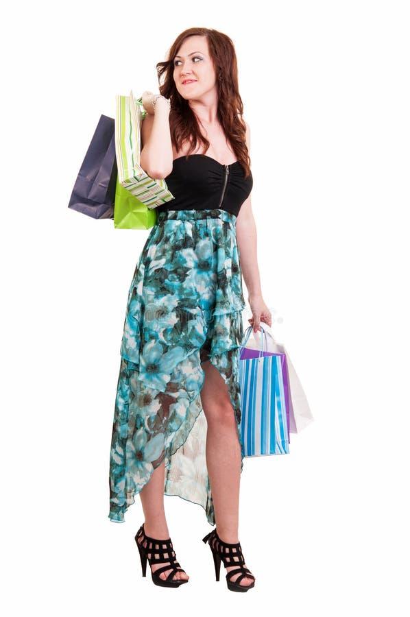 拿着许多购物袋的充分的身体的美丽的妇女被激发 免版税图库摄影