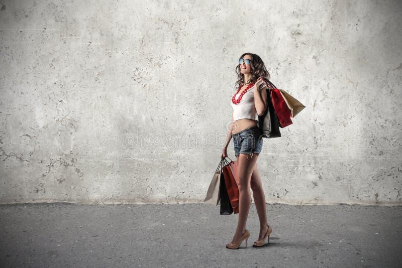 拿着许多购物袋的愉快的女孩 免版税库存图片
