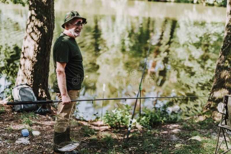 拿着设备的全长一个专业钓鱼者 库存图片