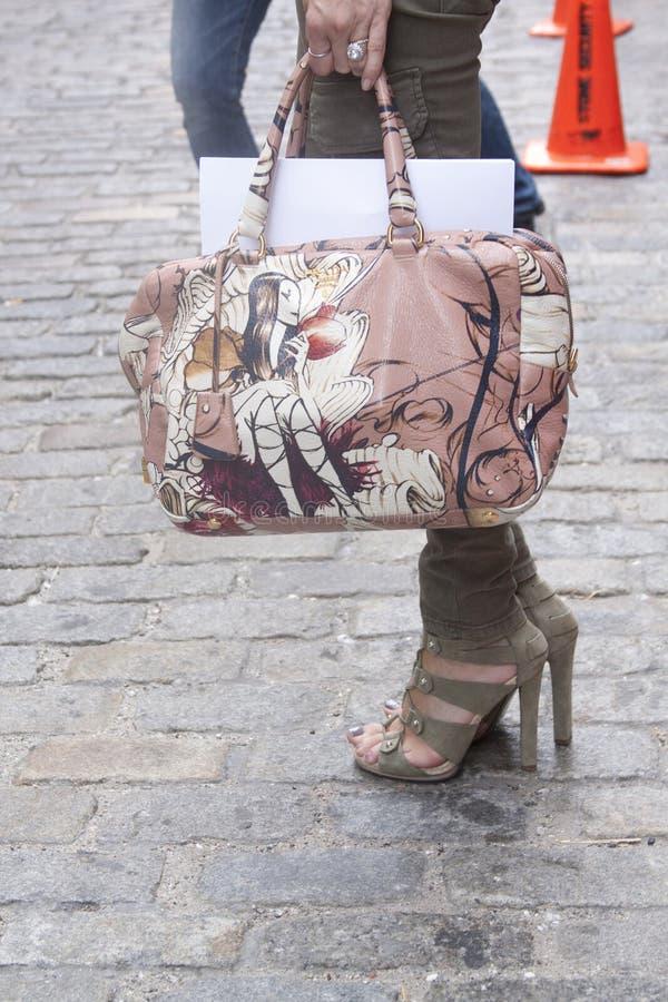 拿着设计师提包和佩带赃物的妇女 免版税库存图片