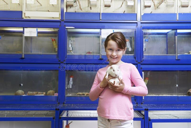 拿着试验品的女孩在宠物商店 免版税库存图片