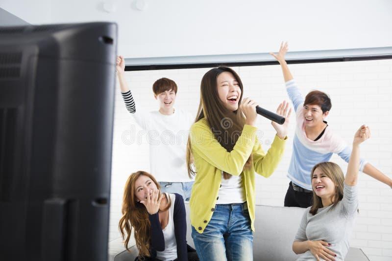 拿着话筒和唱歌在卡拉OK演唱的妇女 免版税图库摄影