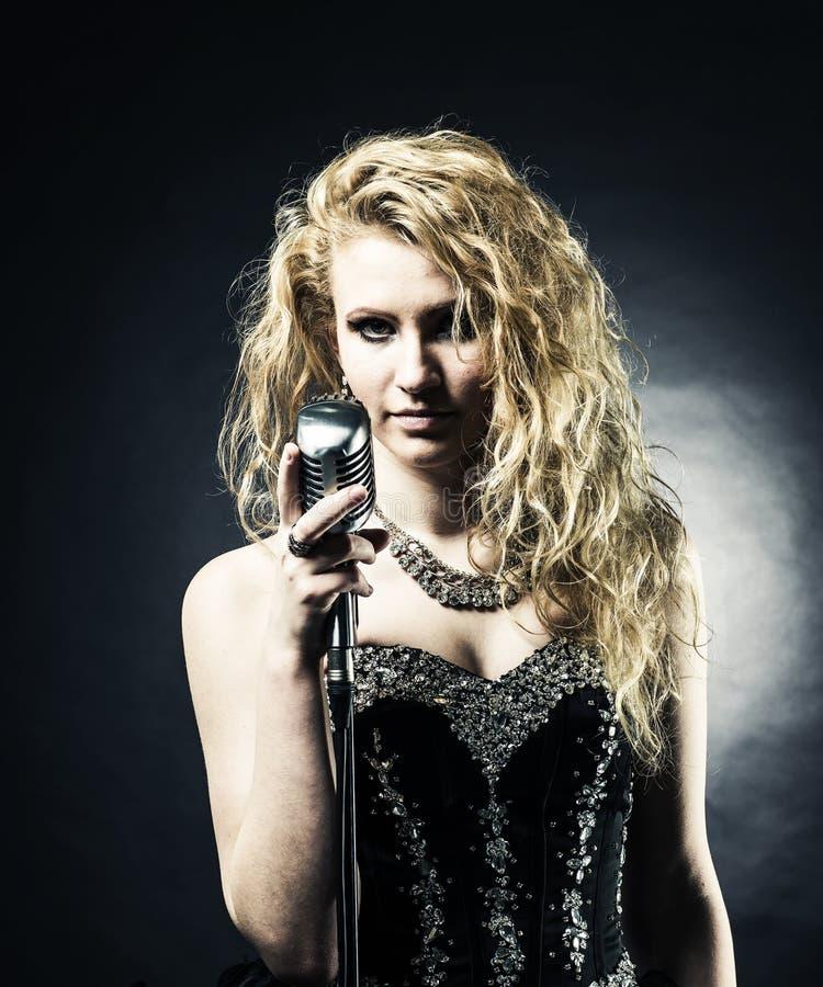 拿着话筒的一件黑礼服的美丽的白肤金发的妇女歌手和唱歌曲 免版税库存照片