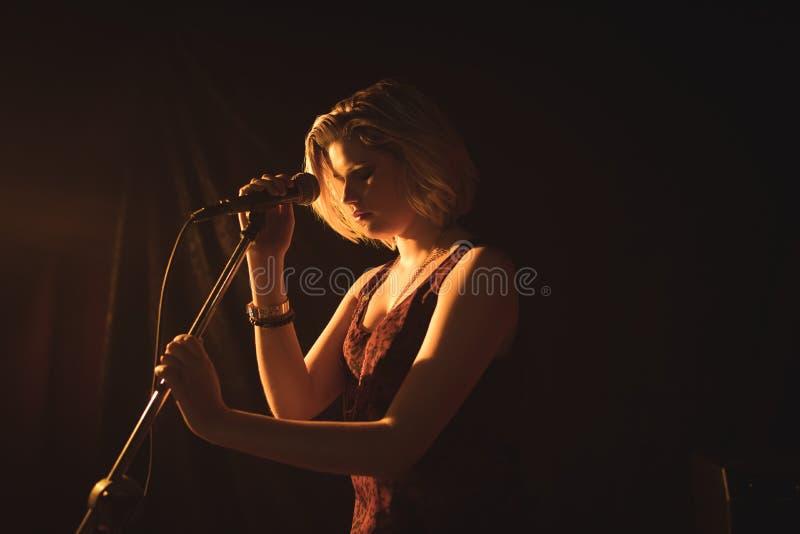 拿着话筒的女歌手在夜总会 免版税库存照片