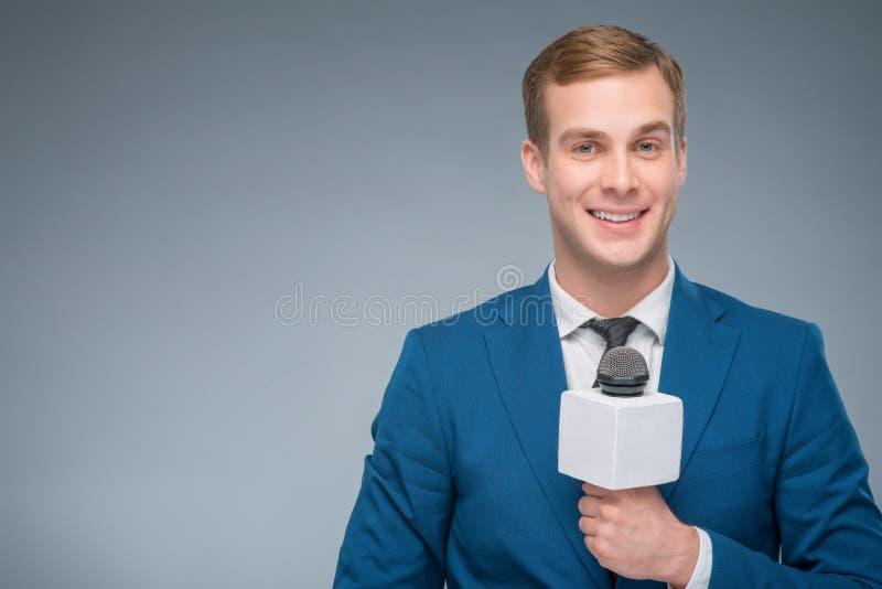 拿着话筒的微笑的新闻记者 免版税库存图片
