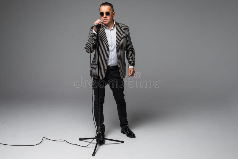拿着话筒的愉快的老人,隔绝在白色背景 库存图片