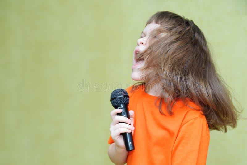 拿着话筒的美丽的女孩唱歌和跳舞 免版税库存图片
