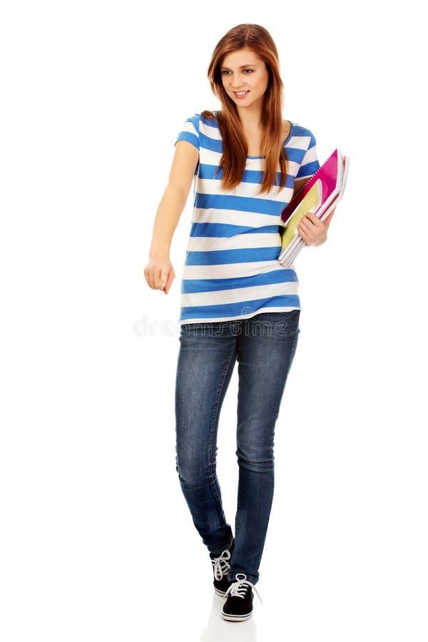 拿着课本和指向为某事的少年愉快的妇女 库存图片
