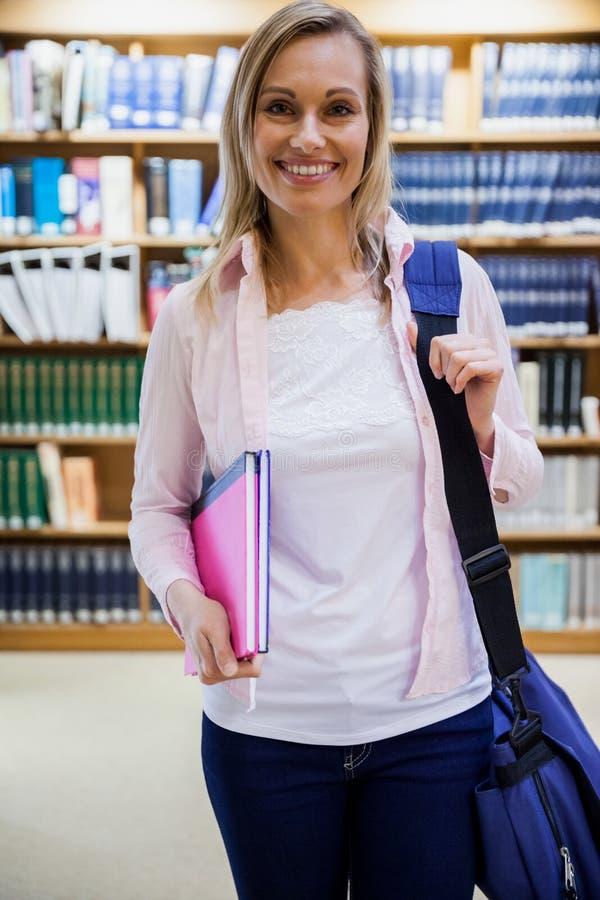 拿着课本的女学生在图书馆里 免版税库存图片