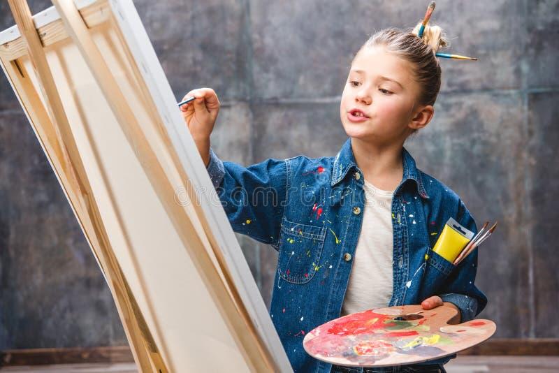 拿着调色板和绘画的小女性艺术家 免版税库存图片