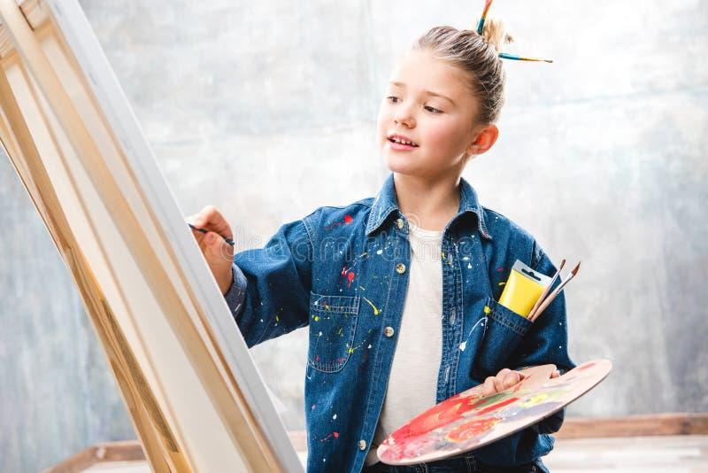拿着调色板和绘画的小女性艺术家 图库摄影