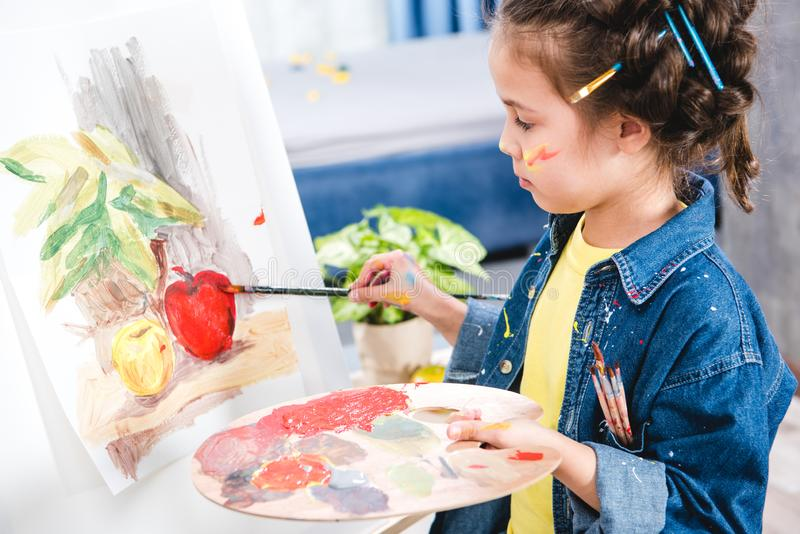 拿着调色板和绘画的小艺术家 免版税库存图片