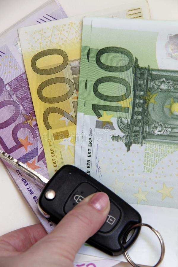 拿着豪华新的汽车钥匙和欧洲钞票的妇女手 免版税库存图片