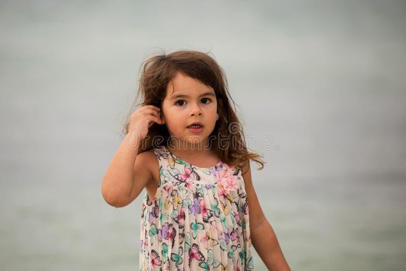 拿着贝壳的逗人喜爱的小女孩 免版税库存图片