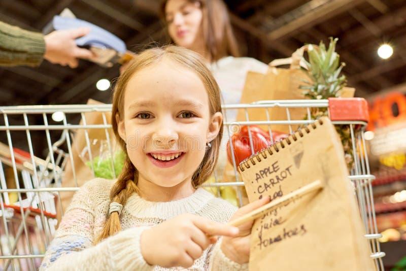 拿着购物单的愉快的小女孩 库存照片