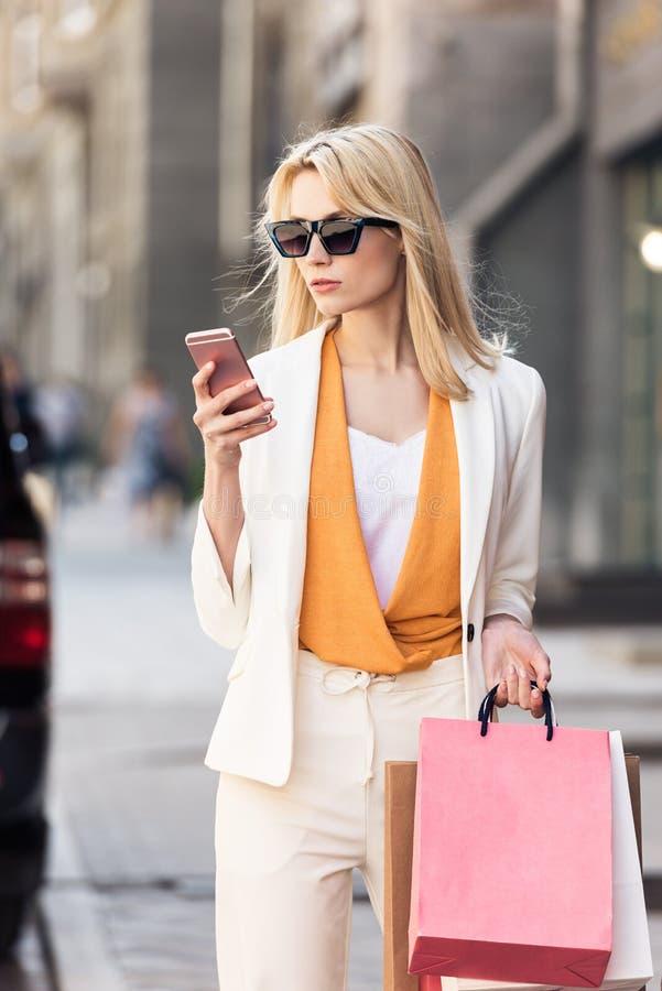 拿着购物带来和使用智能手机的太阳镜的时髦的白肤金发的妇女 免版税库存照片