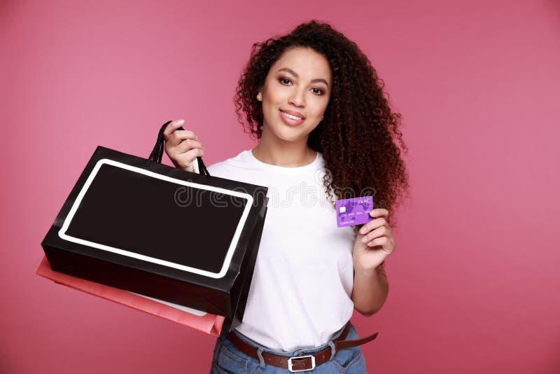 拿着购物带来和显示信用卡的一名激动的年轻非洲妇女的画象被隔绝在米黄背景 库存照片