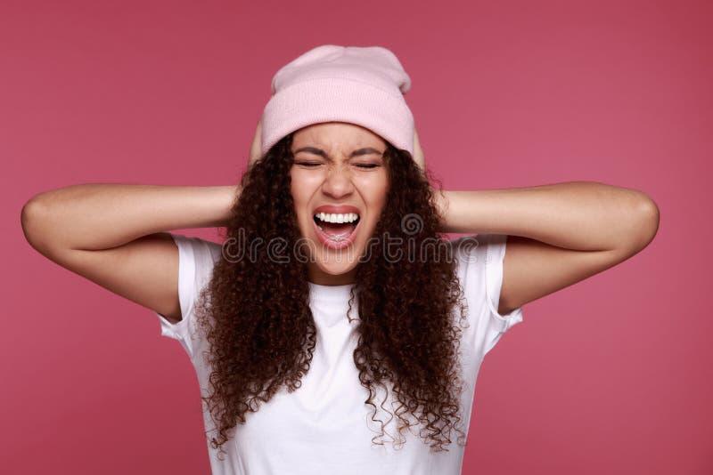 拿着购物带来和显示在米黄背景的一名激动的年轻非洲妇女的画象信用卡 库存图片