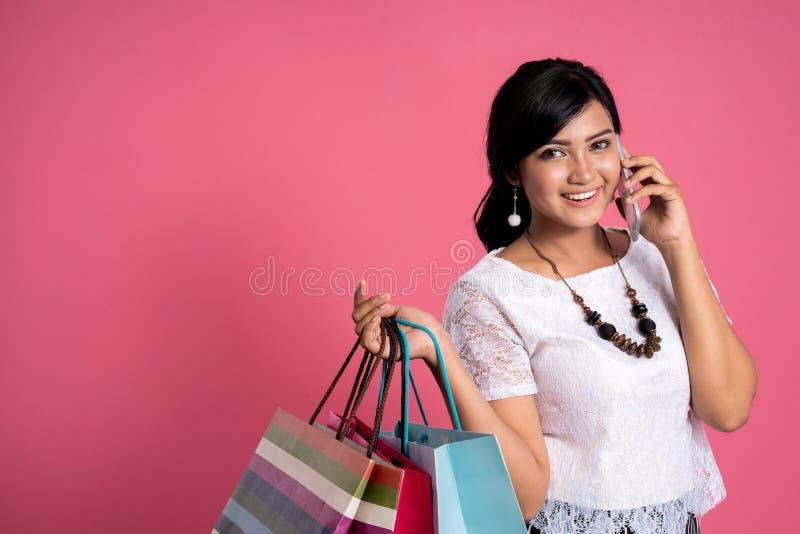拿着购物带来和电话的亚裔妇女 免版税图库摄影