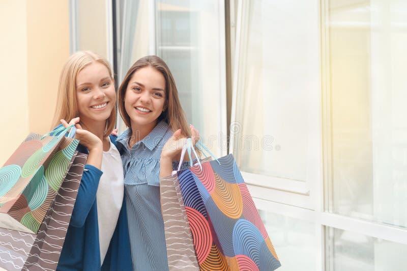 拿着购物带来的两名年轻俏丽的时髦的妇女 免版税图库摄影