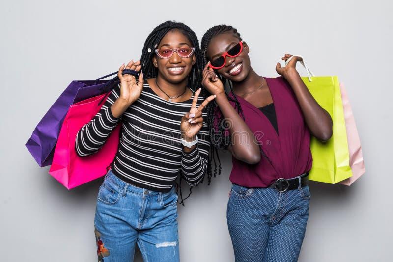 拿着购物带来的两非洲少女画象被隔绝在白色背景 免版税库存照片