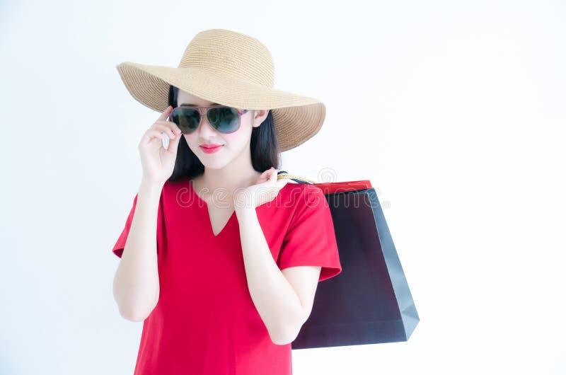 拿着购物带来的年轻美丽的时兴的亚裔妇女戴红色礼服、太阳镜和帽子在白色背景演播室 图库摄影