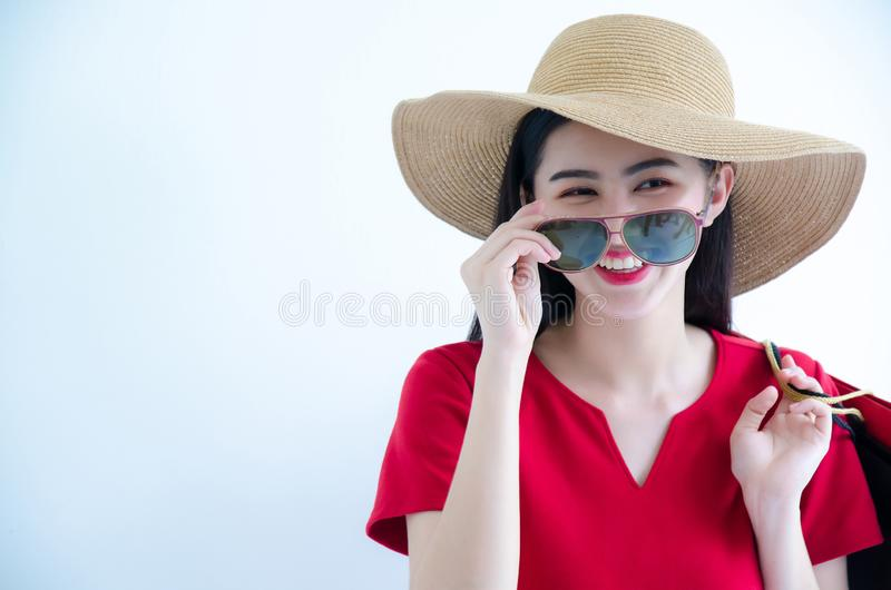 拿着购物带来的年轻美丽的时兴的亚裔妇女戴红色礼服、太阳镜和帽子在白色背景演播室 免版税库存图片