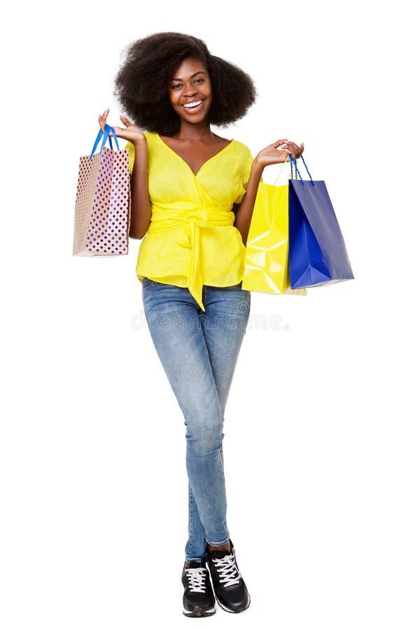 拿着购物带来的微笑的年轻黑人妇女充分的身体画象  库存图片