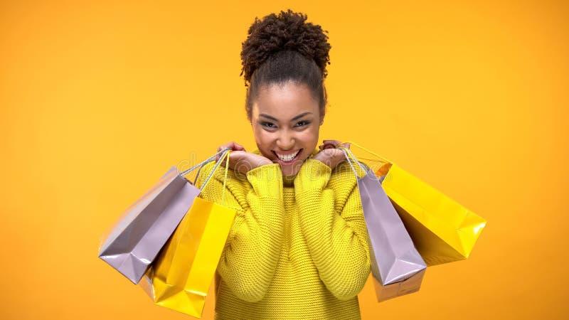 拿着购物带来,折扣的时髦的黄色毛线衣的激动的年轻女人 免版税库存照片