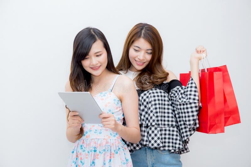 拿着购物袋和片剂计算机的亚裔美丽的年轻人两人妇女画象  免版税库存图片