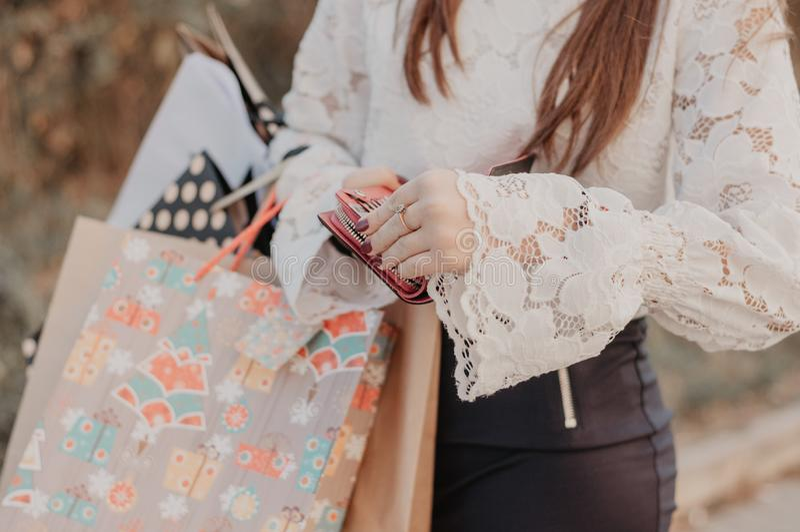 拿着购物袋和皮革黑钱包的妇女 图库摄影