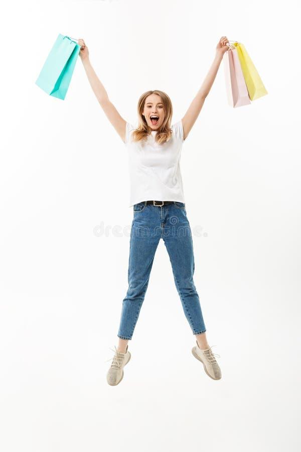拿着购物袋的一个愉快的俏丽的女孩的全长画象,当跳跃和看被隔绝的照相机时 库存照片