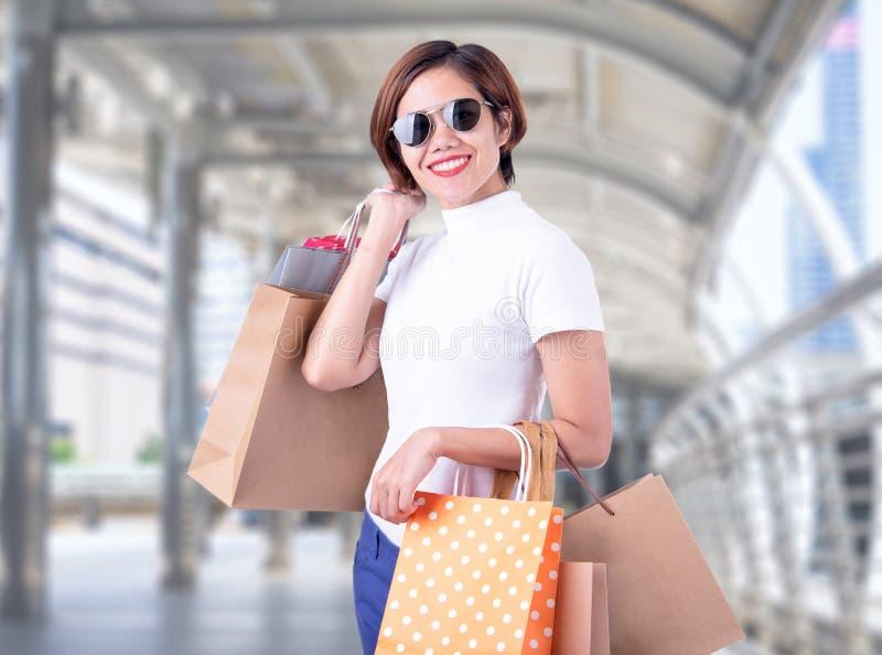 拿着购物袋的一副激动的美丽的亚裔女孩佩带的礼服和太阳镜的画象,当站立在时尚购物中心时 免版税图库摄影