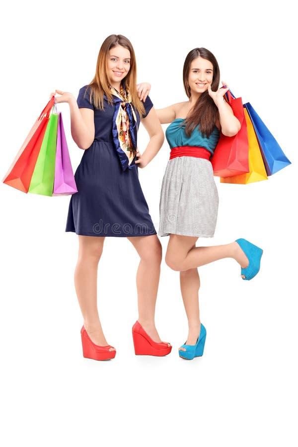 拿着购物袋的二个新女性全长纵向  库存图片