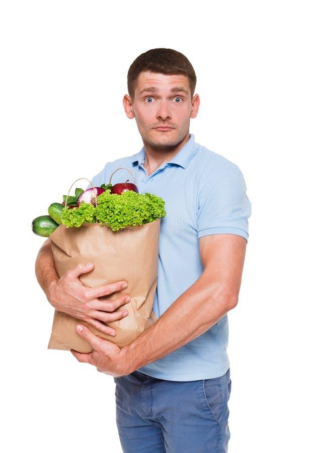 拿着购物袋的年轻人在白色背景隔绝的有很多菜 图库摄影