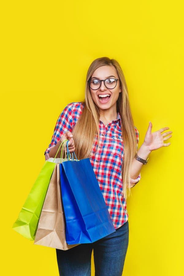拿着购物袋的年轻俏丽的惊奇的妇女Ortrait,隔绝在黄色背景 库存照片