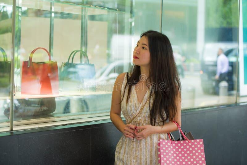 拿着购物袋的年轻美丽和典雅的亚裔韩国妇女在买的走在看衣物窗口sto的街道上以后 免版税库存照片