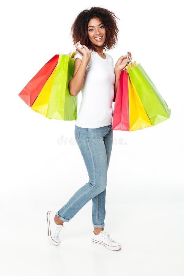 拿着购物袋的愉快的年轻非洲妇女 库存图片