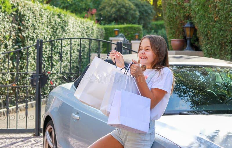 拿着购物袋的愉快的激动的青春期前的女孩停留微笑和享用礼物和礼物的近的汽车 免版税库存照片