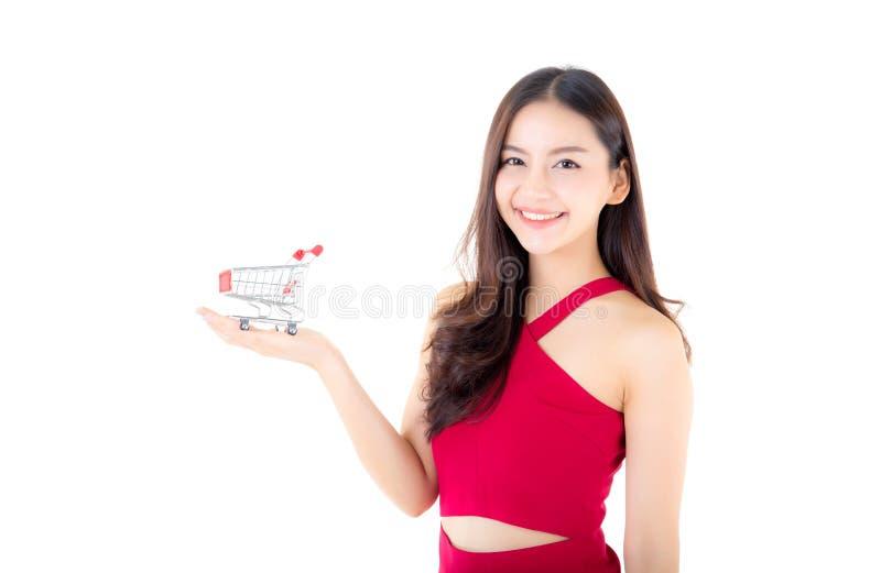 拿着购物车的红色礼服的微笑的亚裔妇女 图库摄影