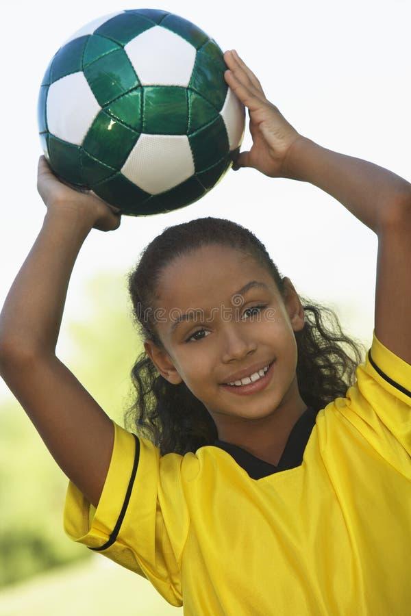 拿着足球的女孩 免版税库存照片