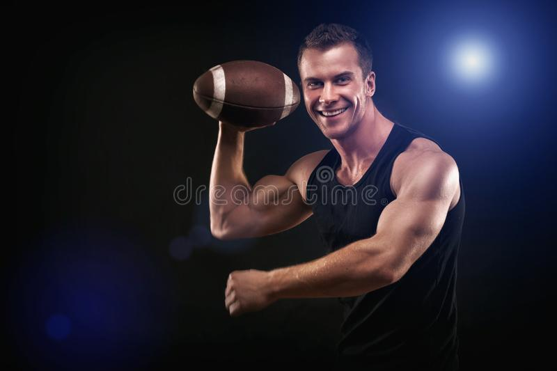 拿着足球的愉快的肌肉年轻人 库存照片