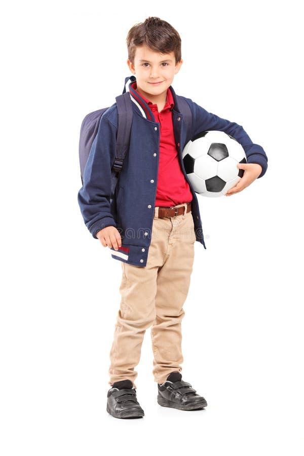 拿着足球的男小学生的全长画象 免版税库存图片