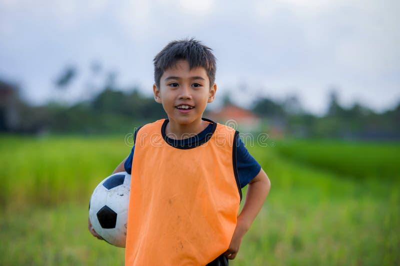 拿着足球的英俊和愉快的年轻男孩生活方式画象踢橄榄球户外在绿草领域微笑的chee 免版税库存照片