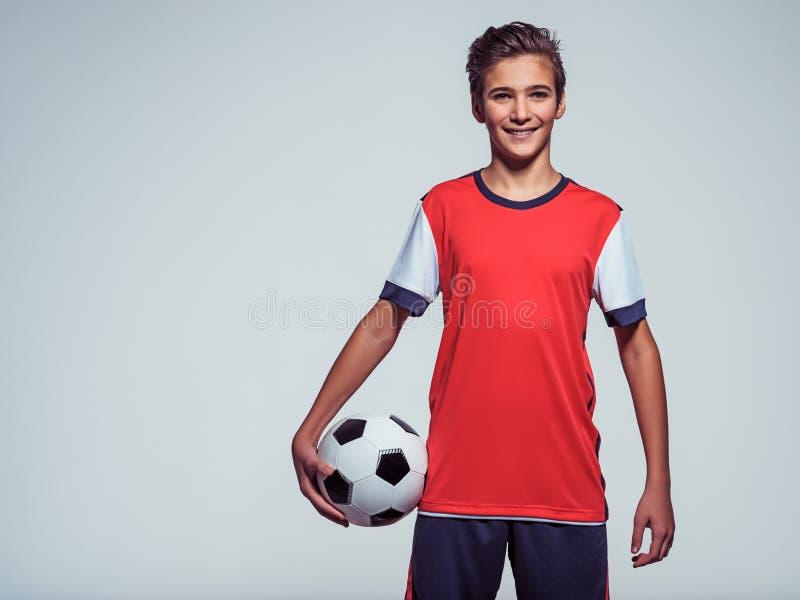 拿着足球的运动服的微笑的青少年的男孩 库存照片